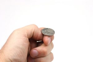 A hand holding a quarter just about to flip a coin.