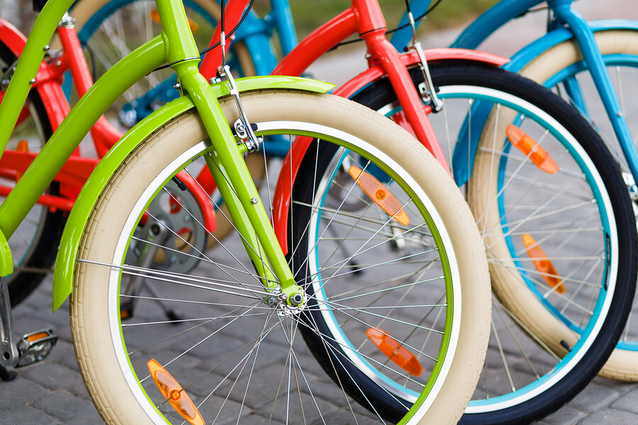 Closeup of three bright colored city urban woman bikes tires row outdoors in the park