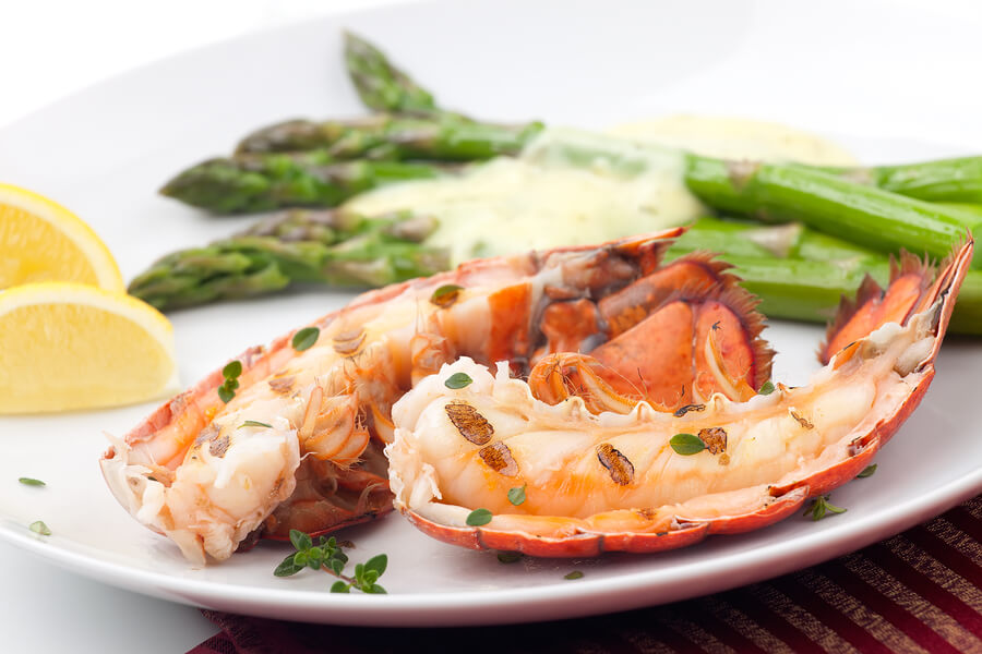 Closeup of delicious grilled lobster tails served with asparagus and bearnaise sauce