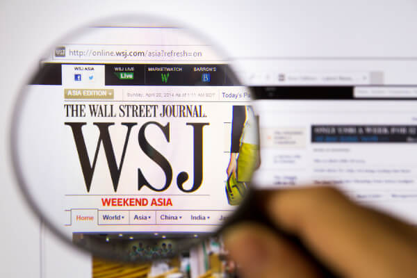Bangkok Thailand APRIL 20 2014: Photo of The Wall Street Journal Monitor homepage on a monitor screen through a magnifying glass.