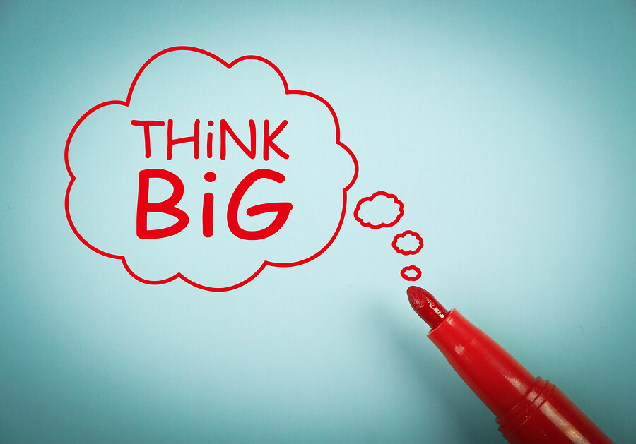 Think big concept is on blue paper with a red marker aside.