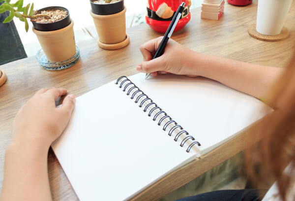 Concept of woman hands with pen writing on notebook